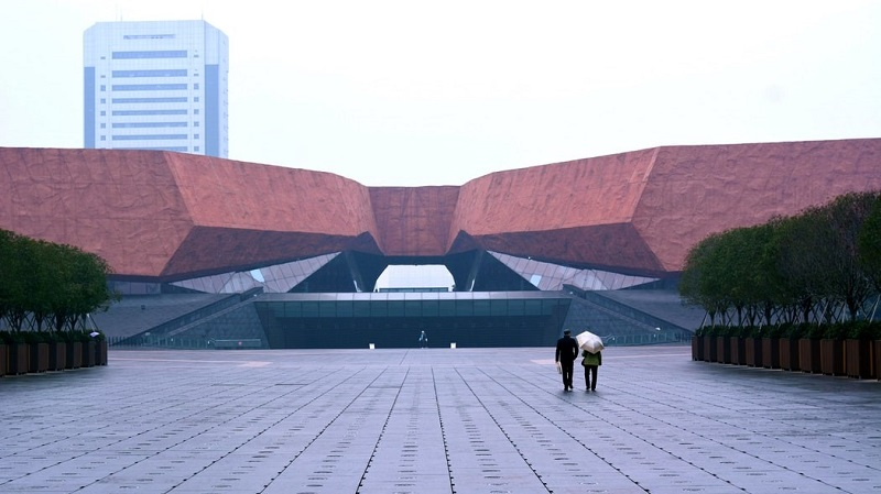 Two people walk in the center of Wuhan, the epicenter of the COVID-19 outbreak