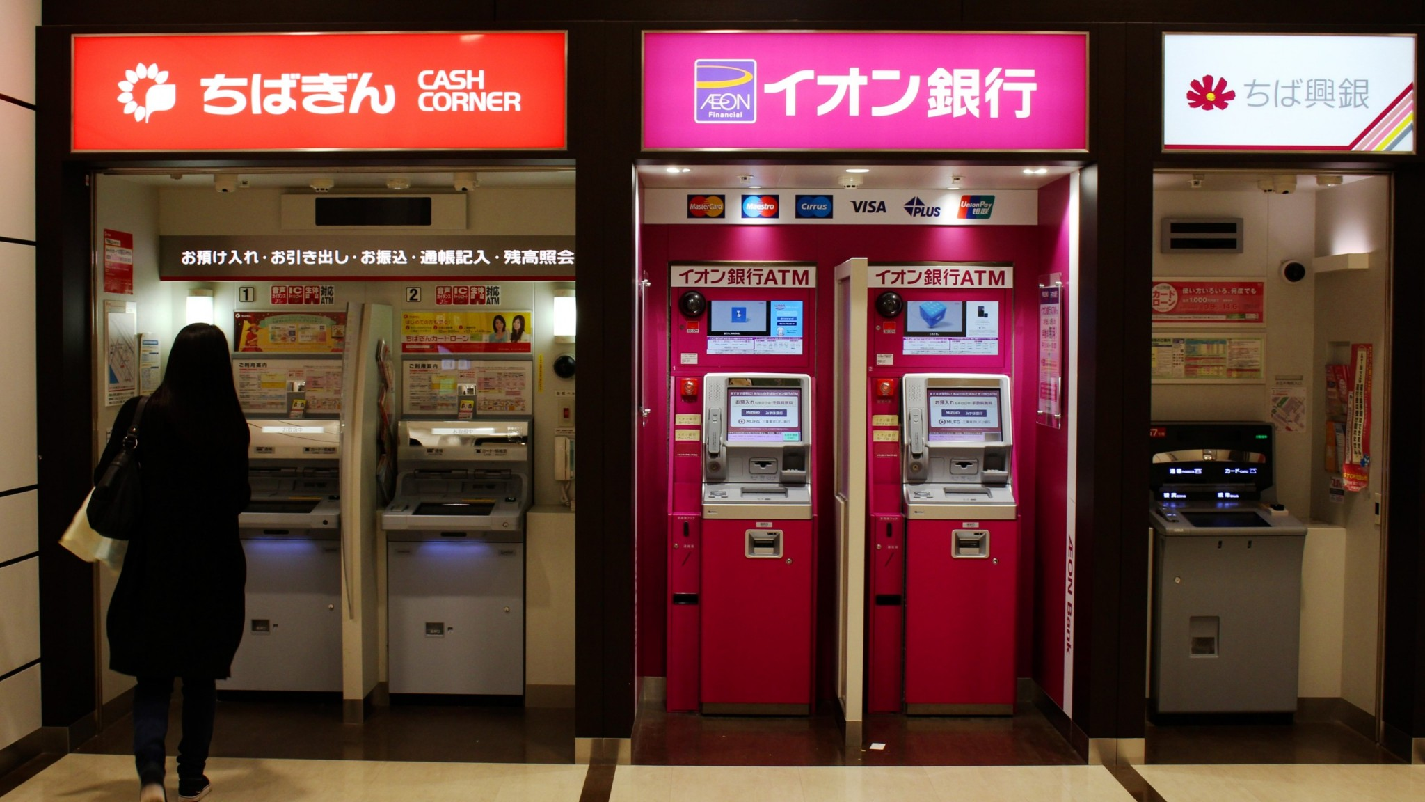 A customer approaches a row of ATMs (including Chiba Ginko and Aeon Ginko) in an Aeon Mall in Makuhari. Japanese regional banks are under pressure due to demographic shifts and the COVID-19 pandemic.