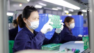 Chinese workers wear masks to produce circuit boards in a factory