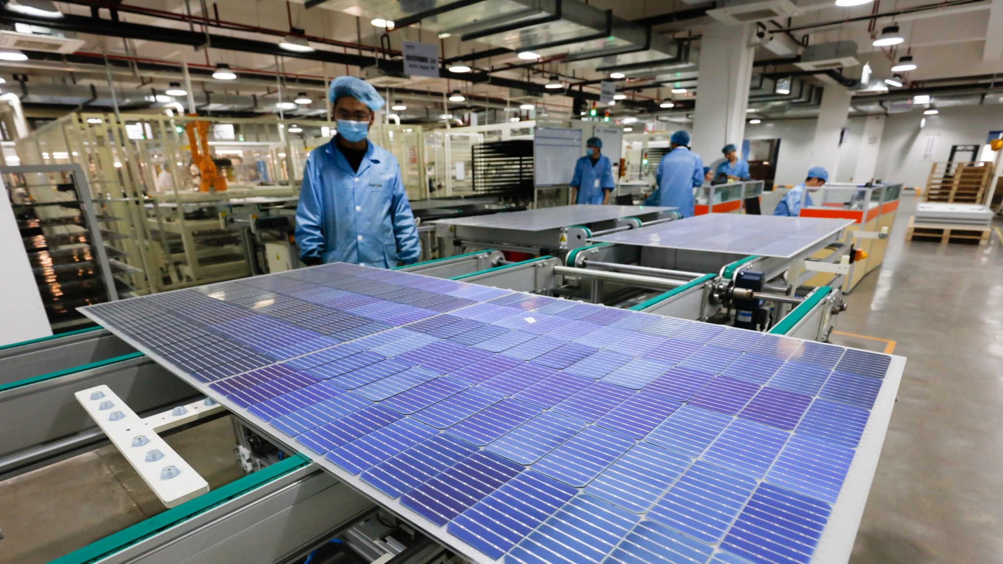 Workers operate equipment to produce photovoltaic circuit boards at a production workshop of a green energy technology company